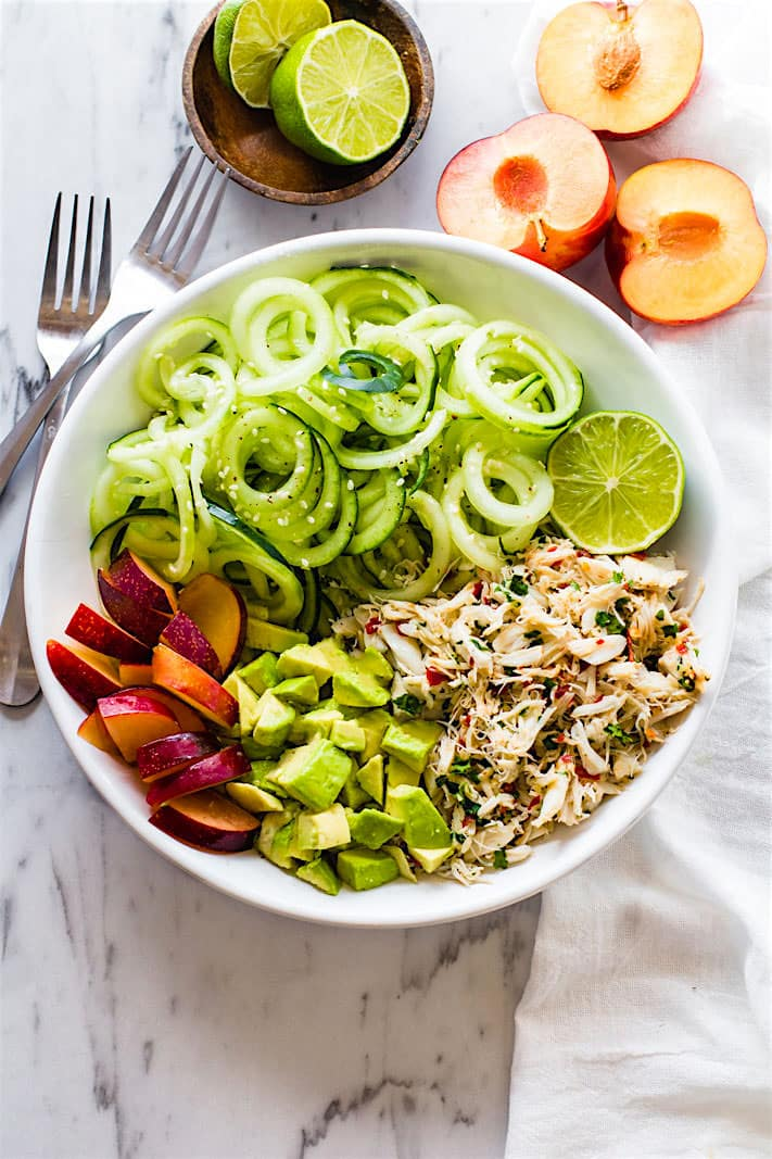 Seafood lovers rejoice! You'll love this Power Lunch Paleo Asian Crab and Avocado Spiralized Cucumber Salad! Light, Gluten Free, and Super Healthy crab and zesty spiralized cucumber salad topped with avocado and juicy plum. Protein packed and nutrient dense!