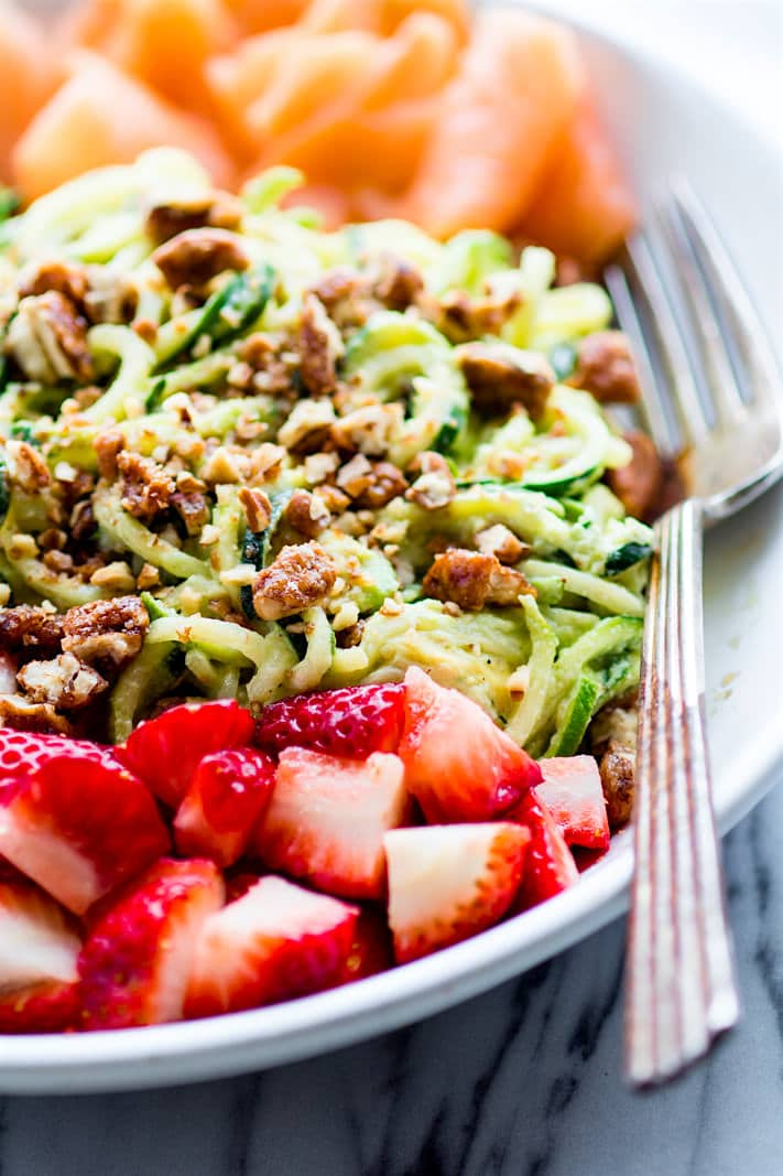 Smoked Salmon and Strawberry Zucchini Noodle Pasta Salad! A healthy lower carbZucchini noodle pasta salad witha creamyavocado sauce and paired with the freshstrawberries, spinach, and smoked salmon. This gluten free Salad bowl is perfectfor aspring or summer lunch or side dish. Clean ingredients, real food, UNREAL GOOD!