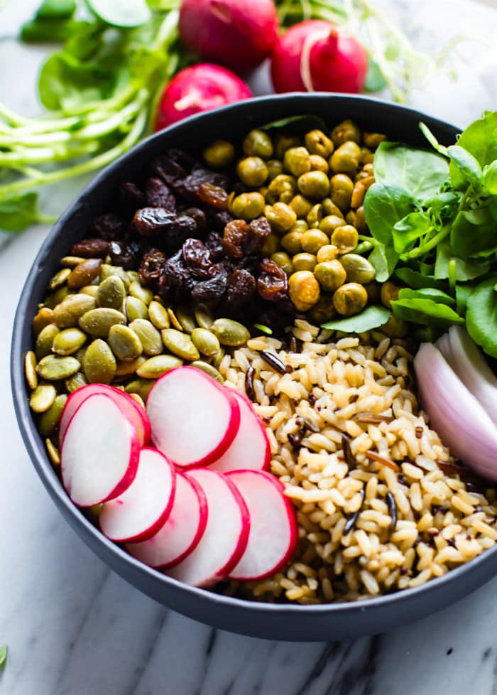 Nourishing Garden Veggie Vegan Buddha Bowl! This wholesome and healthy Buddha bowl recipe, (aka hippie bowls) is filled with ancient, garden veggies, crunchy peas and seeds, and lots of superfood ingredients. A delicious way to get a variety of nutrients packed all in one gluten free bowl!