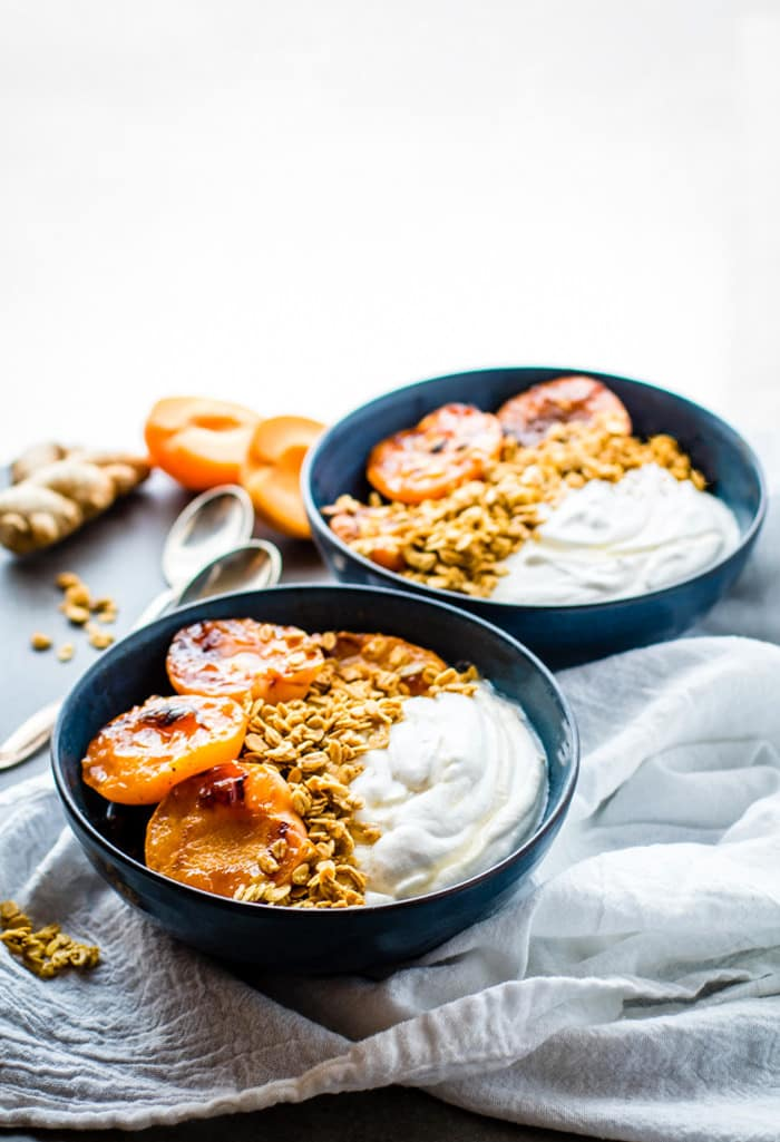 Gluten Free Char-grilled apricot parfait dessert bowls! These dessert bowls are great for dessert or breakfast. A light and simple dessert that's layered across with glazed grilled apricots, whipped coconut cream, and wholesome granola.