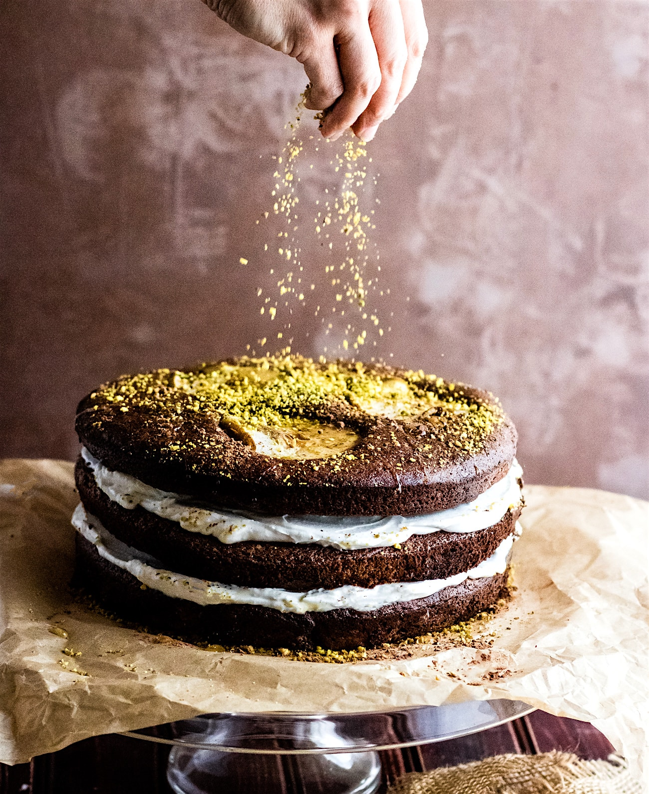 Flourless Chocolate Pistachio Pear Naked Layer Cake. A paleo flourless chocolate layered cake that is light in texture, rich in taste, and delicious! Filled with maple coconut cream then topped with cocoa, glazed pears, and pistachio! This naked cake is simple to make. A decadent dessert that feeds a crowd!