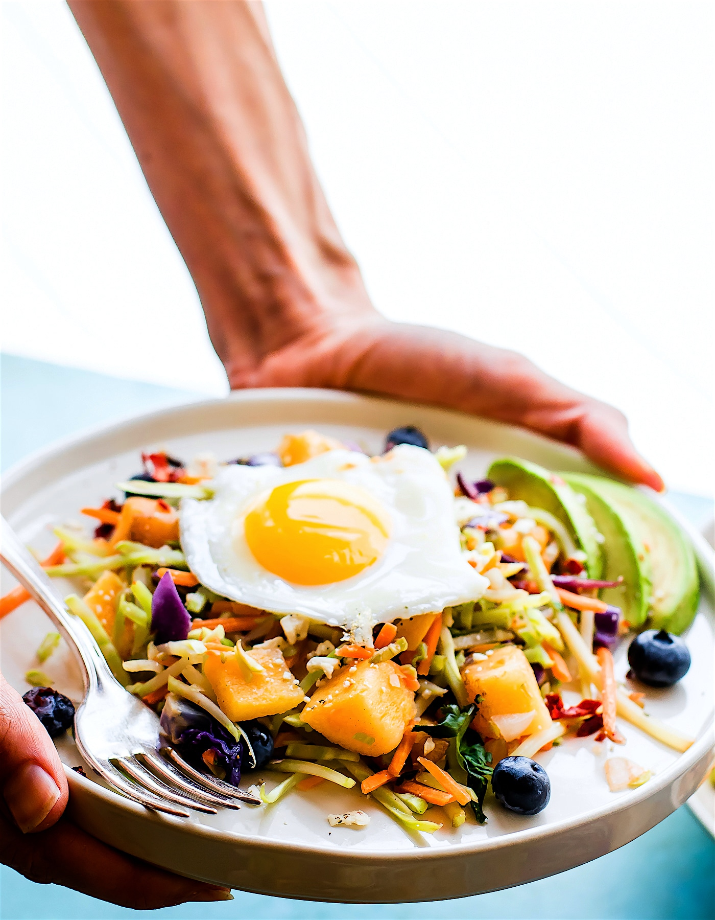 Breakfast salad to start the day! A nourishing warm Paleo meal with broccoli slaw, squash, berries, and fried eggs. A breakfast salad worth waking up for! #whole30