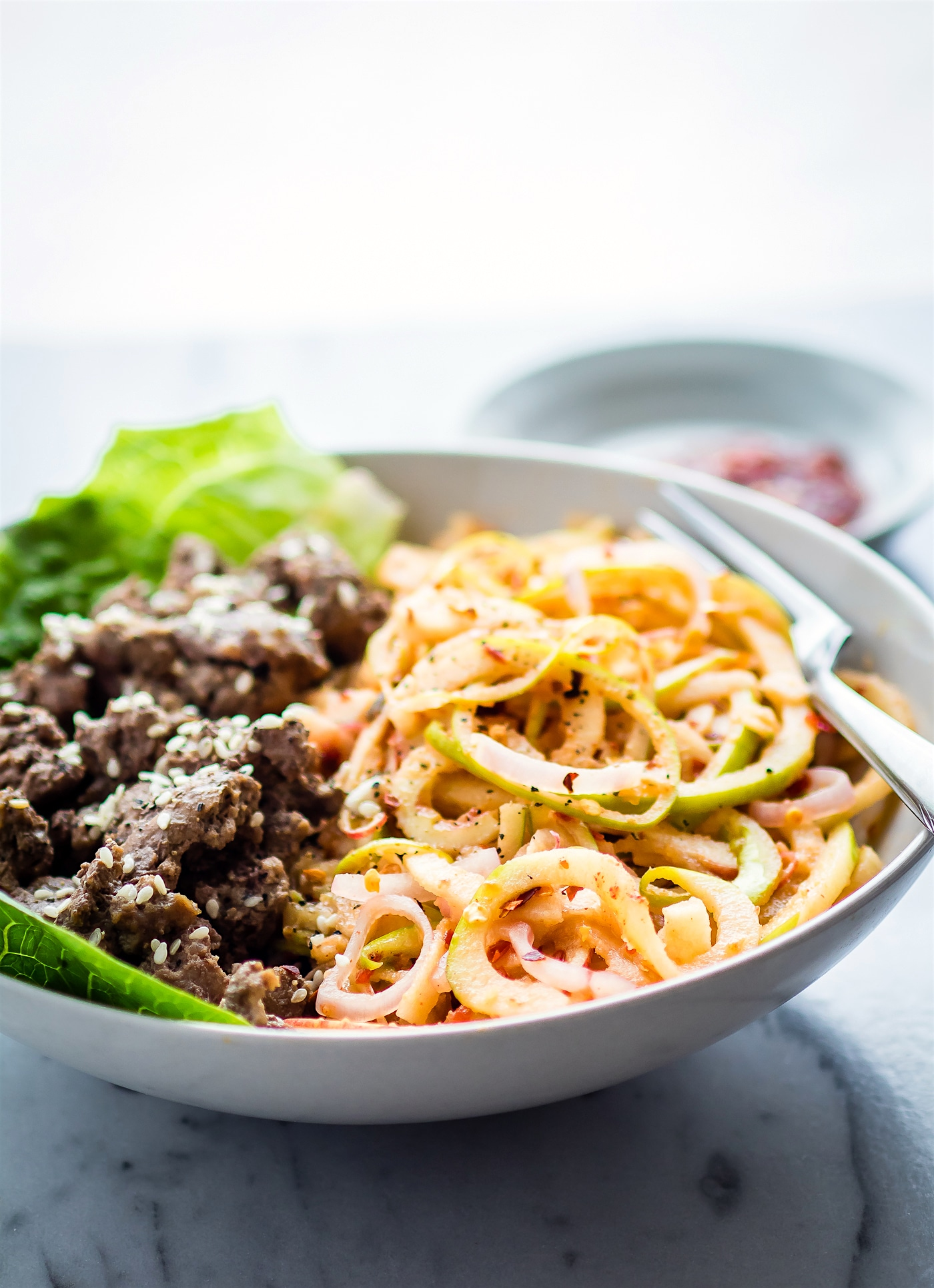 "Spiralized Apple ""kimchi"" salad with Garlic Beef! This Asian inspired spiralized apple salad makes a quick and healthy kimchi substitute. Red and Green Apple noodles combined in a spicy dressing with garlic beef. An easy Paleo power bowl meal ready in 30 minutes!"