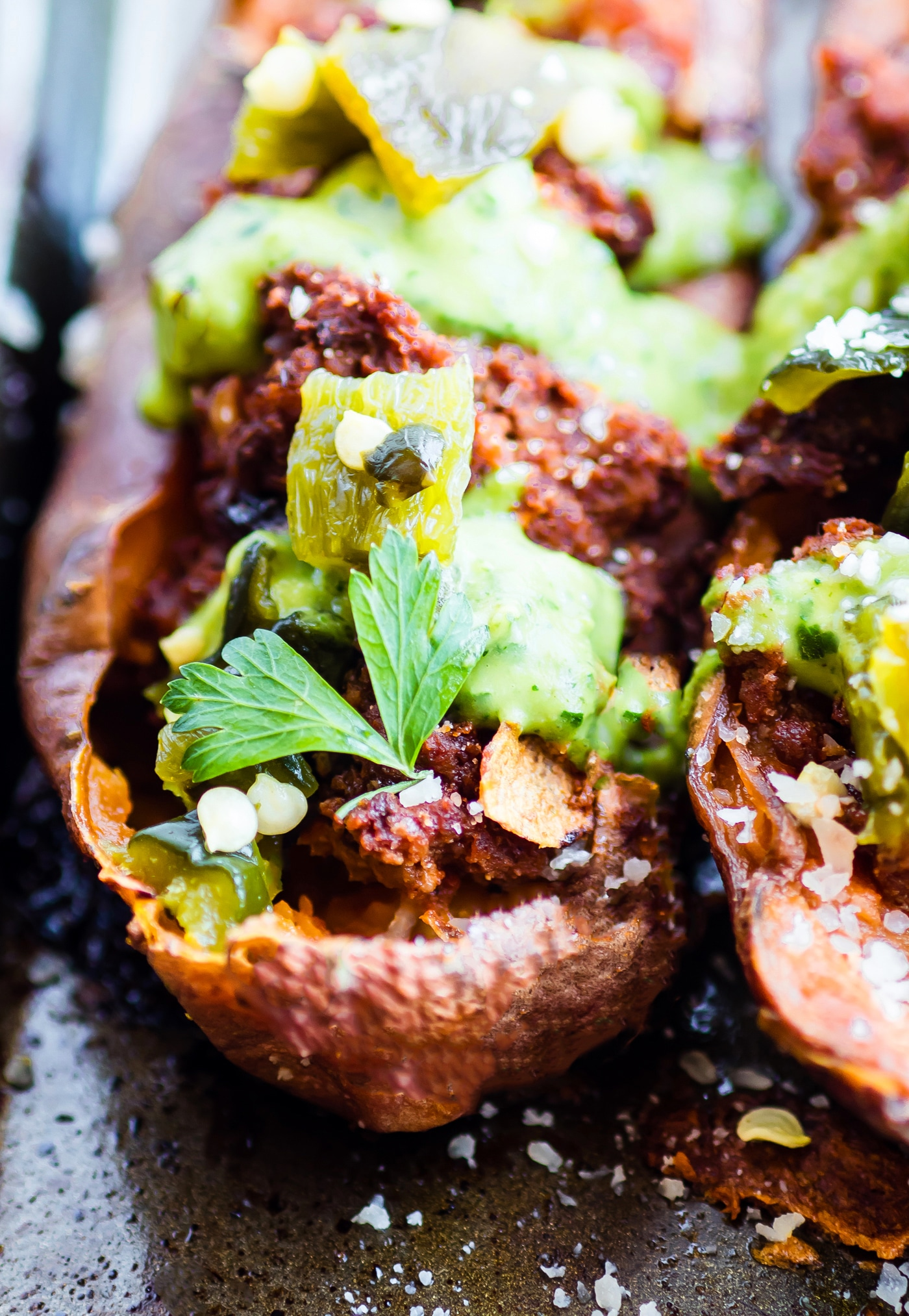 Ancho Beef Chili Stuffed Sweet Potato Skins. A paleo meal or appetizer that is so simple to make and full of flavor! These sweet potato skins are filled to the max with tasty ancho beef chili, chopped and roasted poblanos, and a spicy avocado cream sauce. The best kind of dish to satisfy that hunger. Dairy free, gluten free, and whole 30 friendly ya'll!