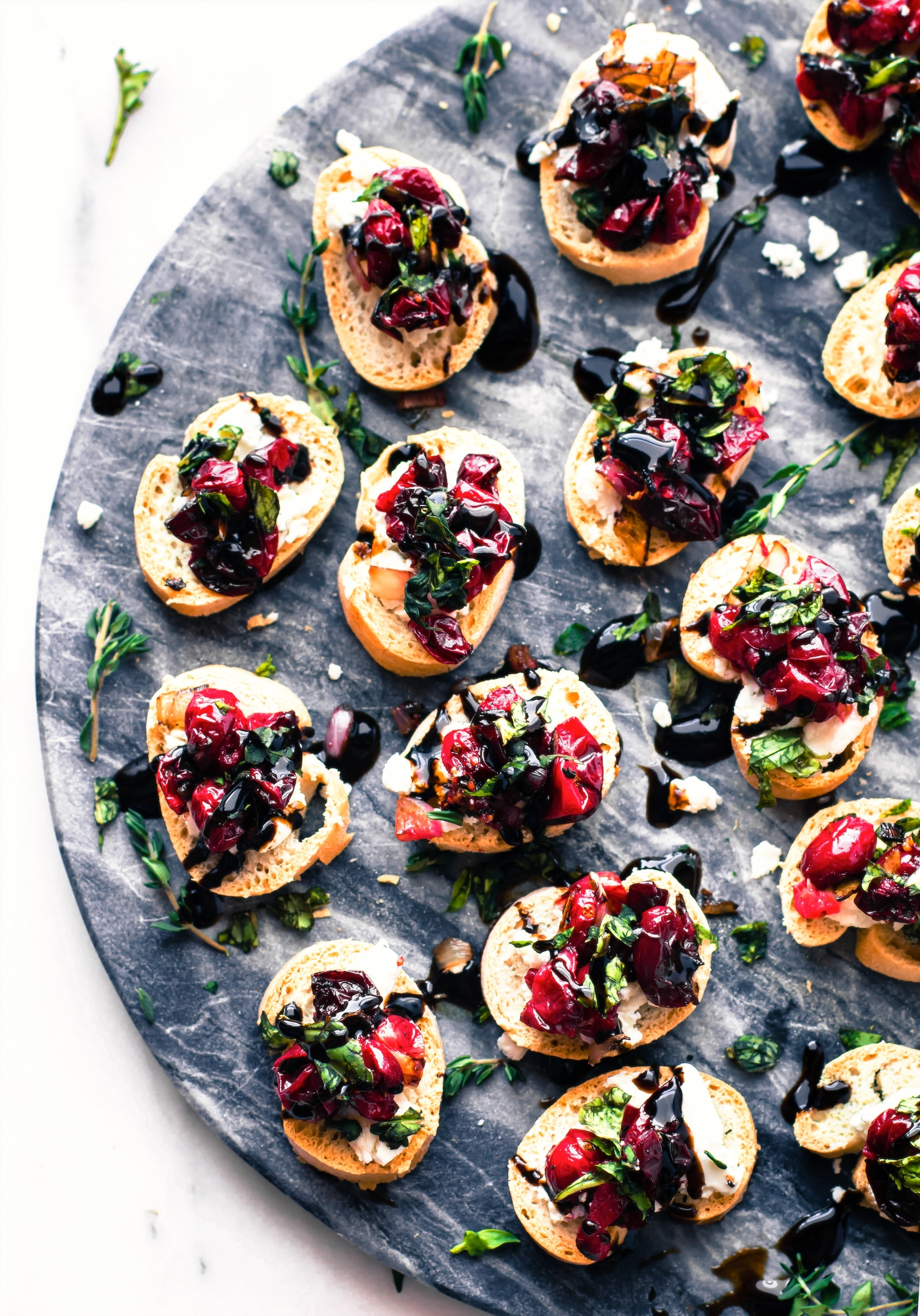 A Gluten Free Crostini baked appetizer recipe for the holidays! Cranberry goat cheese gluten free crostini with roasted balsamic cranberries, onion, basil. www.cottercrunch.com