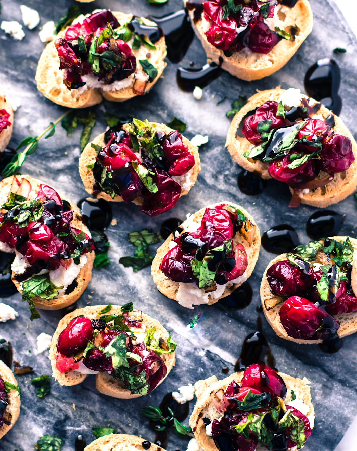 A Gluten Free Crostini baked appetizer recipe perfect for the holidays! This quick cranberry goat cheese gluten free crostini is made with roasted balsamic cranberries, sweet onion, then topped with fresh basil and balsamic glaze. Super quick, easy, healthy, and a delicious! One of my favorite crowd-pleasing appetizers. www.cottercrunch.com