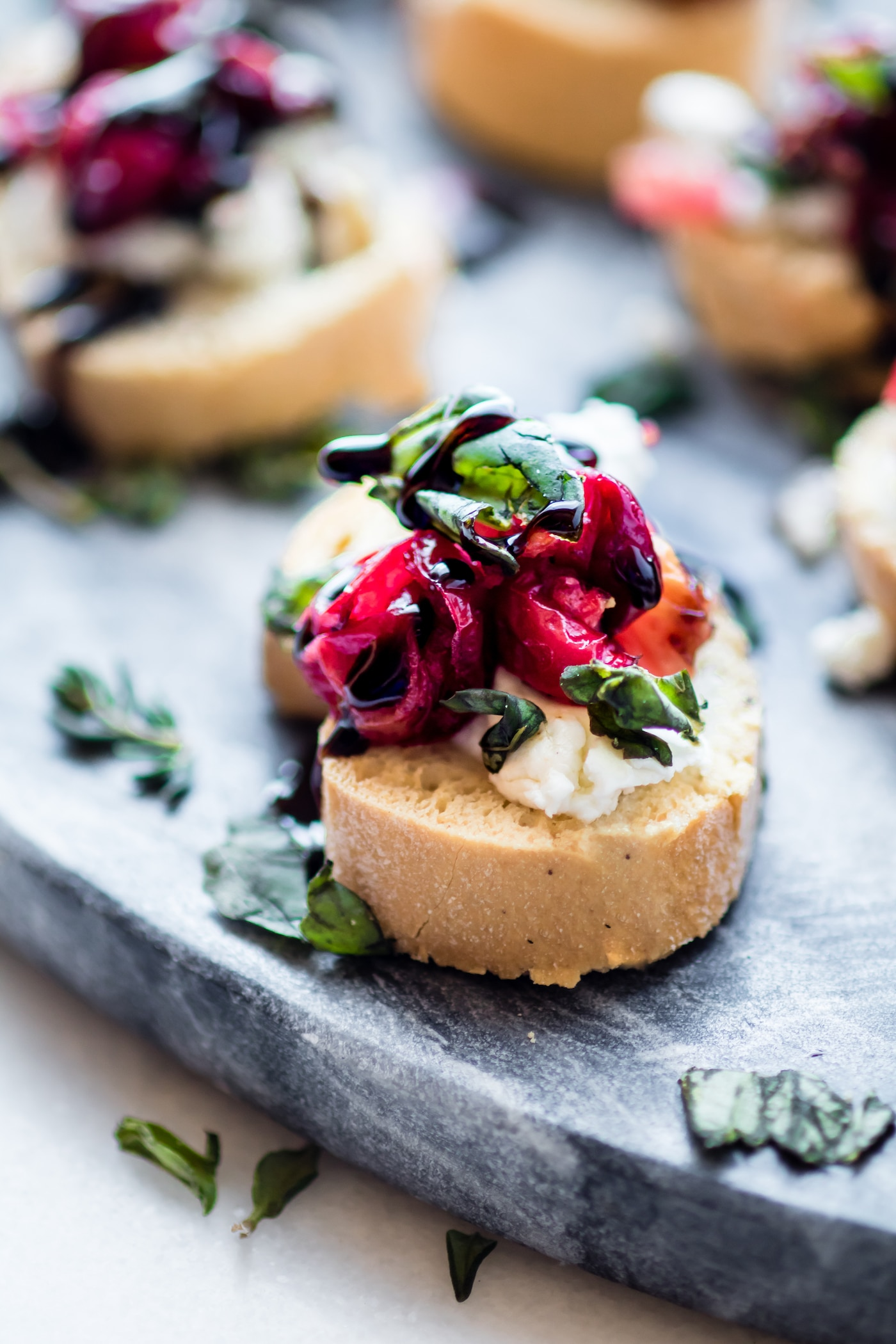 A Gluten Free Crostini baked appetizer recipe perfect for the holidays! This quick cranberry goat cheese gluten free crostini is made with roasted balsamic cranberries, sweet onion, then topped with fresh basil and balsamic glaze. Super quick, easy, healthy, and a delicious! One of my favorite crowd-pleasing appetizers.