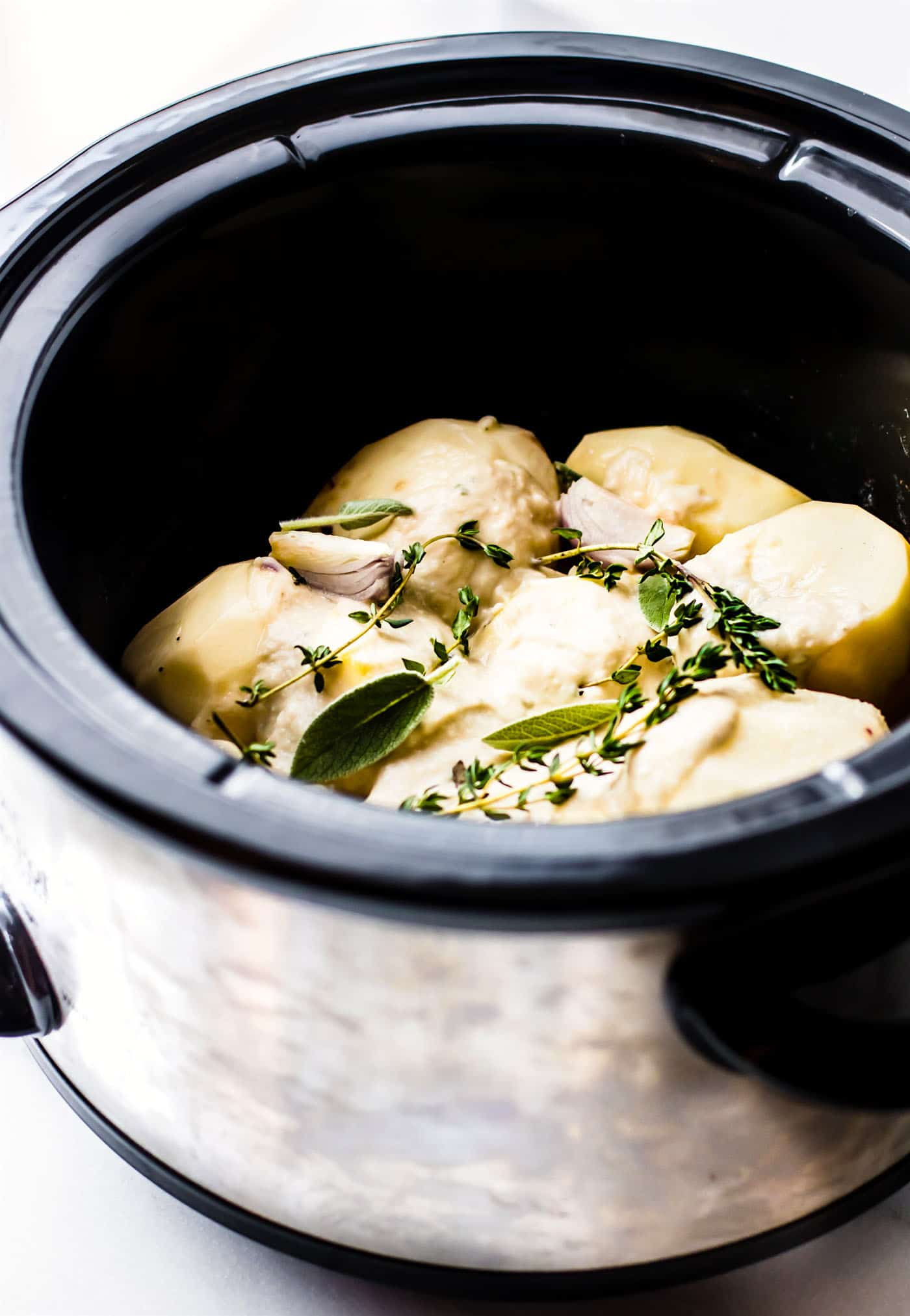 Slow cooker mashed potatoes with a creamy white bean and herb puree! These Vegan slow cooker mashed potatoes are so buttery and delicious, even without the butter! A simple, yet healthy, white bean sage puree is cooked right in to give it extra flavor and texture!. A vegan side dish that everyone will enjoy!