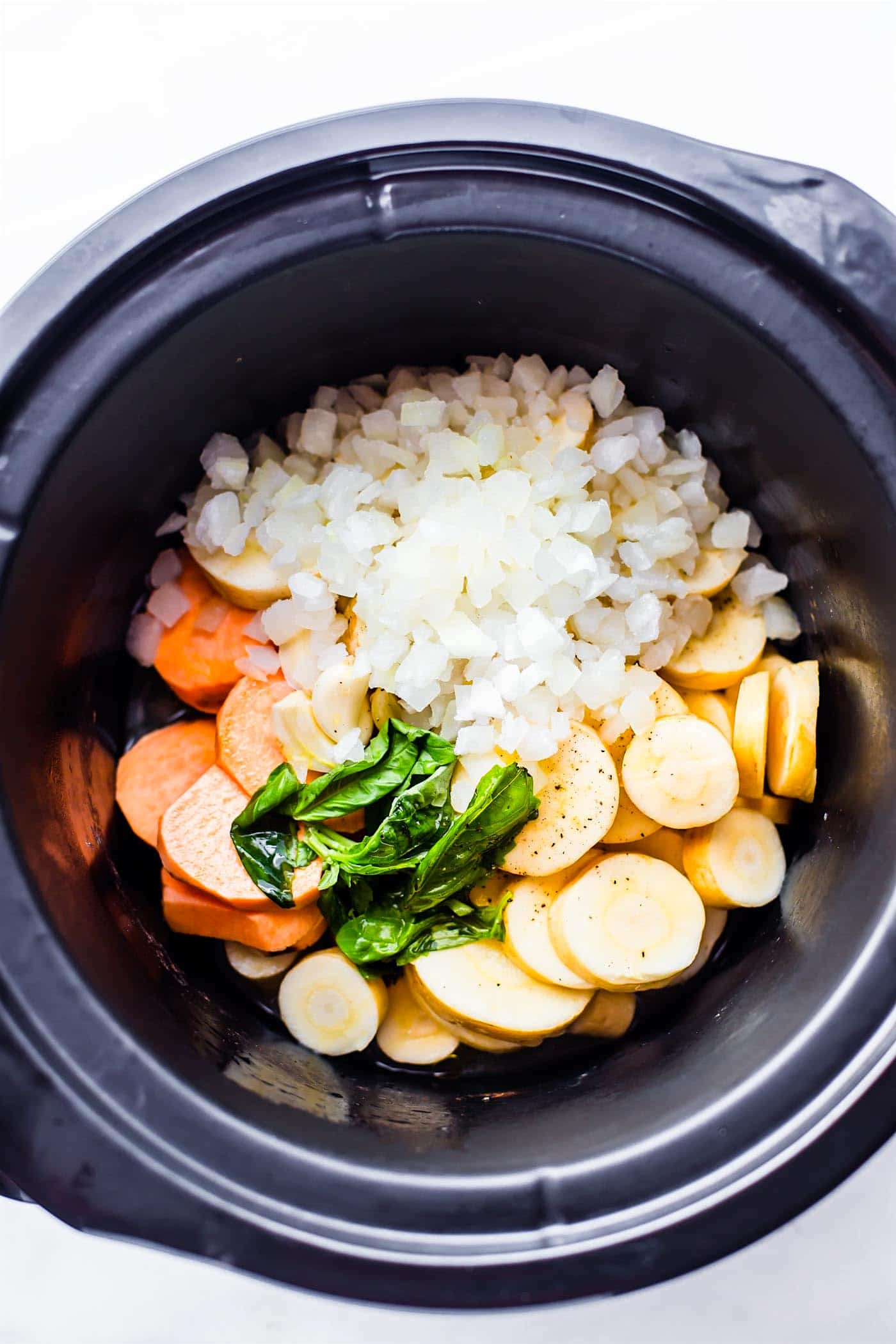 onions, potatoes, parsnips, and carrots in a slow cooker
