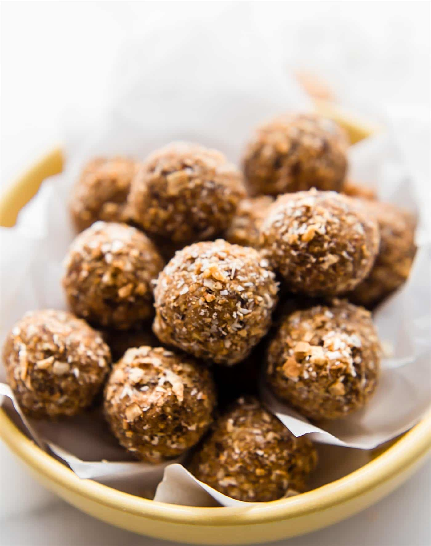 Toasted Coconut Bliss balls. A healthy sweet bliss balls recipe made with dates, cashews, cinnamon toasted coconut, and maple. An easy Paleo & vegan snack or treat.