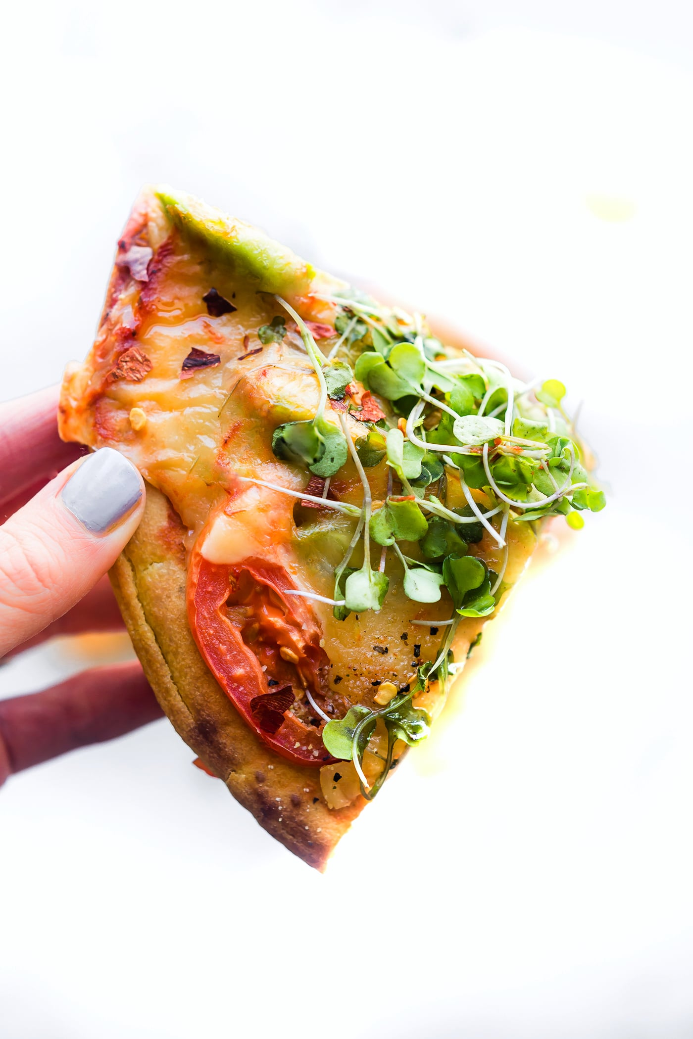 Avocado Tomato Gouda Socca Pizza recipe to love! A grain free, gluten free Avocado Tomato Gouda Socca Pizza made with chickpea flour and topped with Avocado, Gouda, Tomato, and Sprouted Greens! Seriously easy to make, egg free, vegan option, OMG delicious!