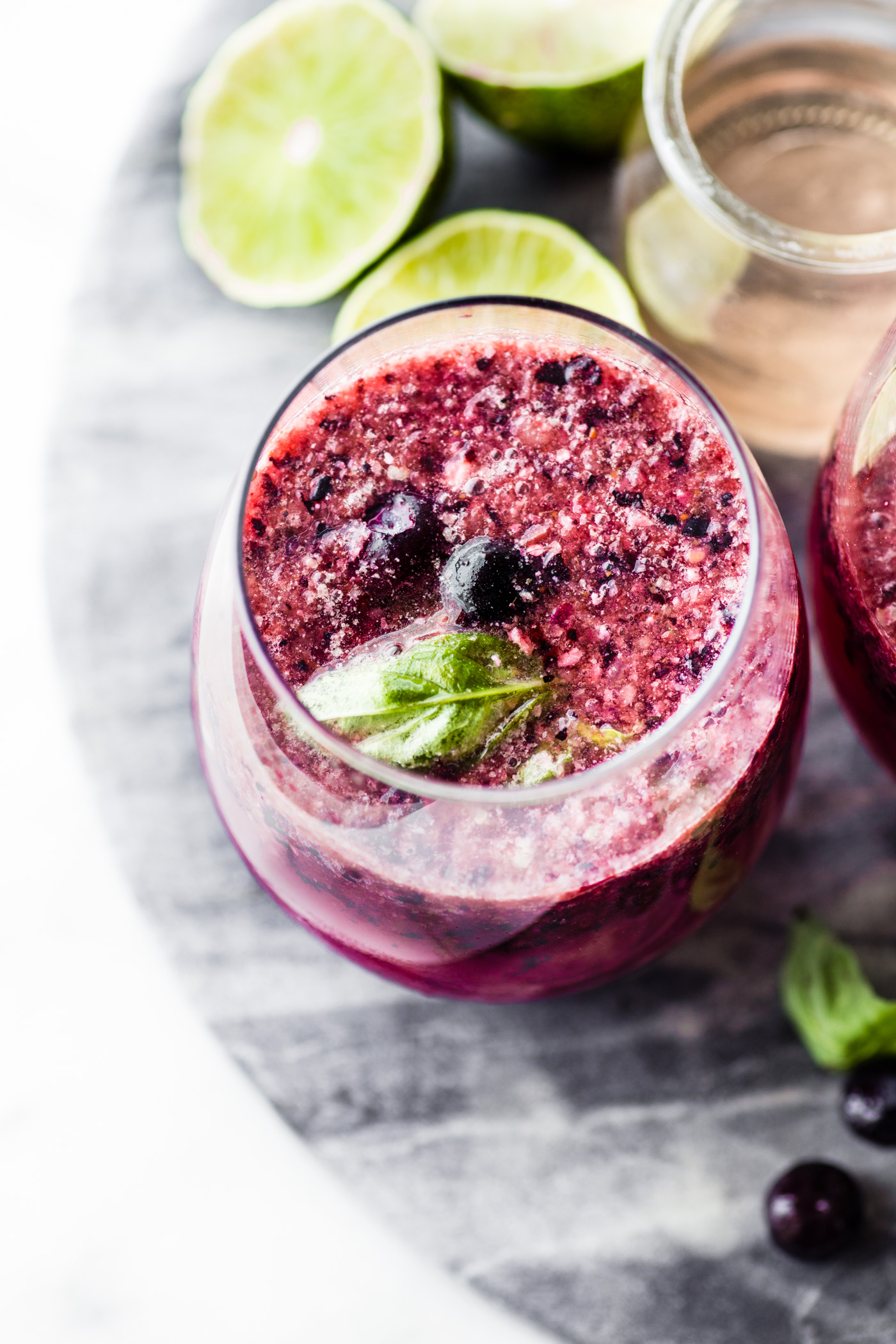 Wine Slushies may be an adults only version of a Slurpee, but this Berry Frosé recipe is lighter, more sophisticated, and BLISSFULLY delicious! Triple Berry Frosé (aka Frozen Rosé wine) wine slushie is blended with fruit, fresh juice, and a hint of basil, creating a fun and refreshing summer cocktail!