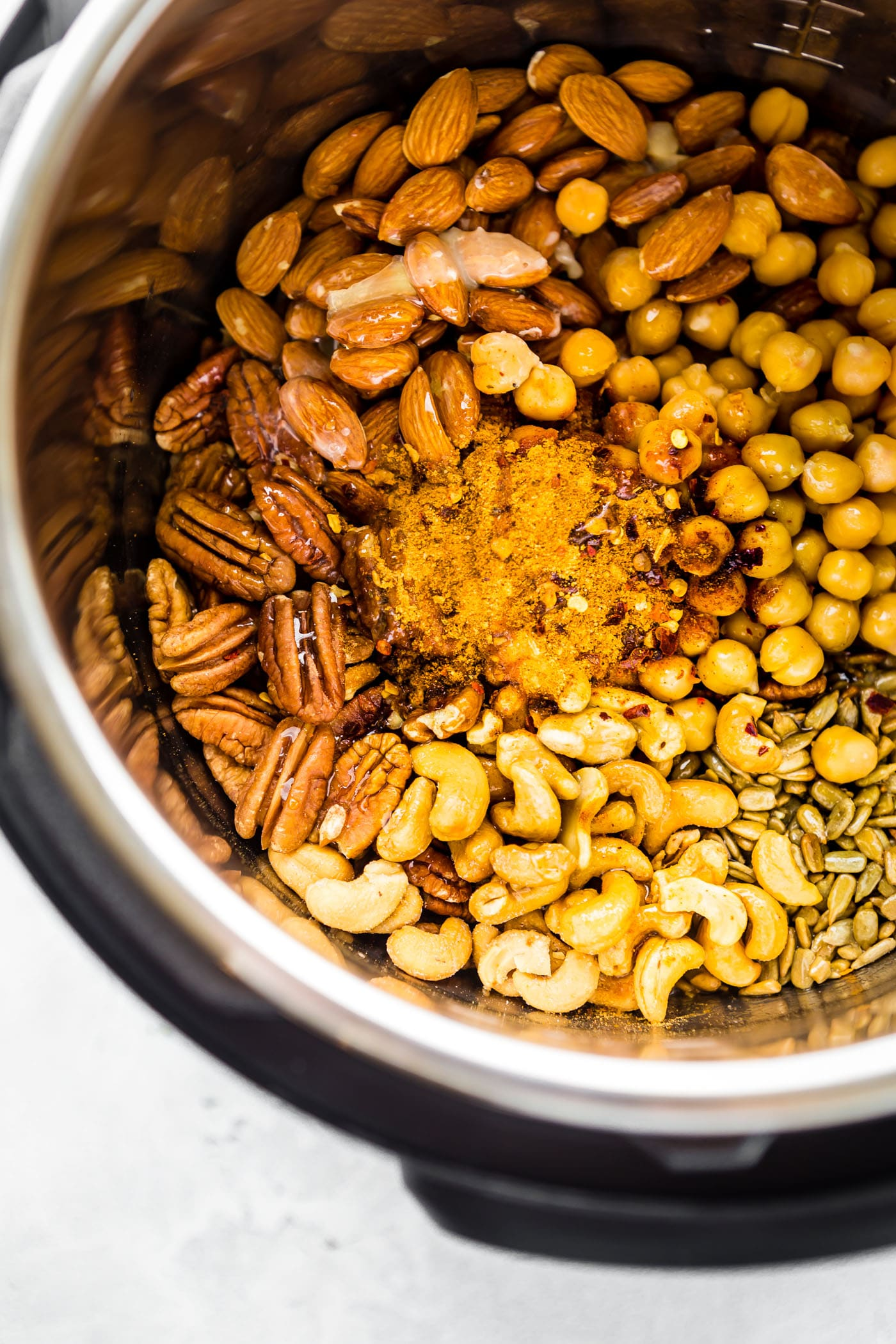 Spicy candied cajun trail mix made easy in the instant pot! What's not to love? This candied cajun trail mix is the perfect quick and healthy snack and total crowd pleaser. Cajun Spices, maple syrup, nuts, seeds, and chickpeas all cooked together then mixed with dried mango for a sweet touch. It's vegan friendly and naturally grain free!