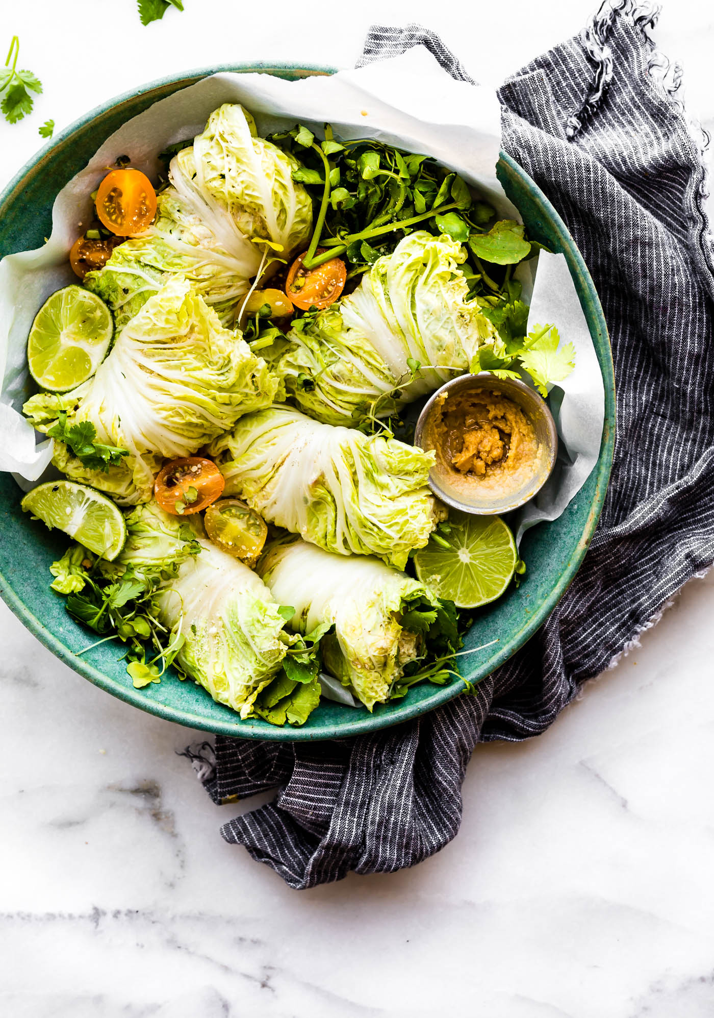 Miso Mango Chicken Salad Cabbage wraps are the perfect light low carb lunch that's easy to make! A mango chicken salad that's mayo free, paleo friendly, and flavorful! Spread the miso mango chicken salad mixture over napa cabbage, add a little bit of watercress, then firmly roll up! Bam, a perfectly handy lunch or light dinner!