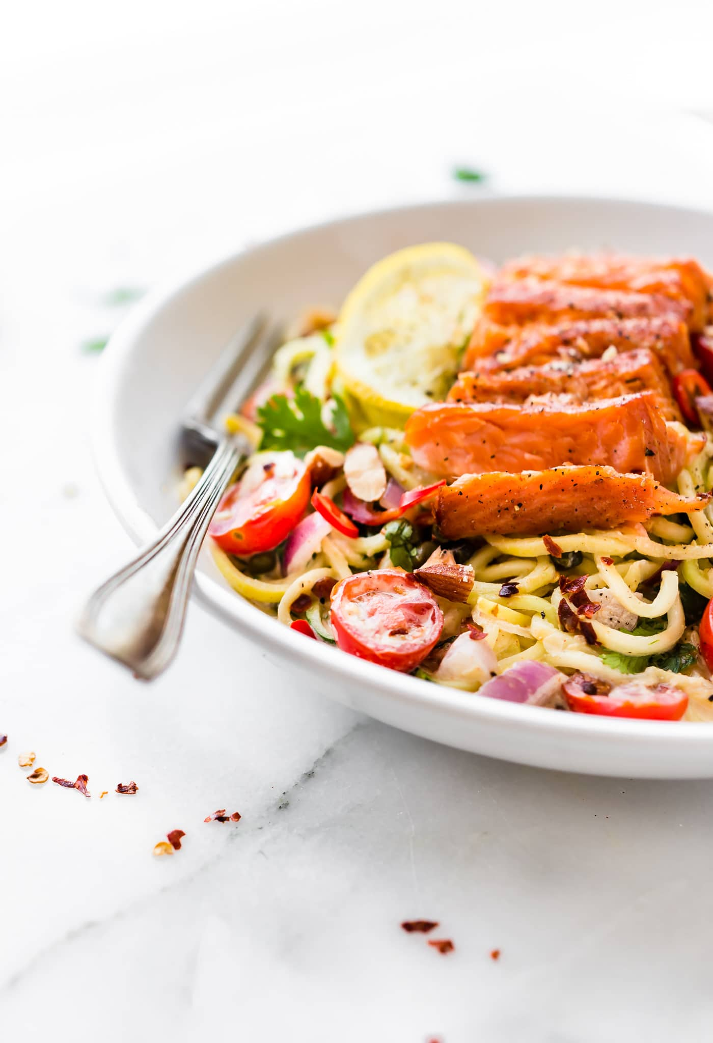 kickin Smoked Salmon Zucchini Noodles salad makes for a perfect no cook meal! Just what we need for Summer, yes? Or anytime really! A zippy cajun sauce tossed in chopped vegetables and zucchini noodles then topped with peppery smoked salmon. It's TO DIE FOR! Paleo and Real food deliciousness!