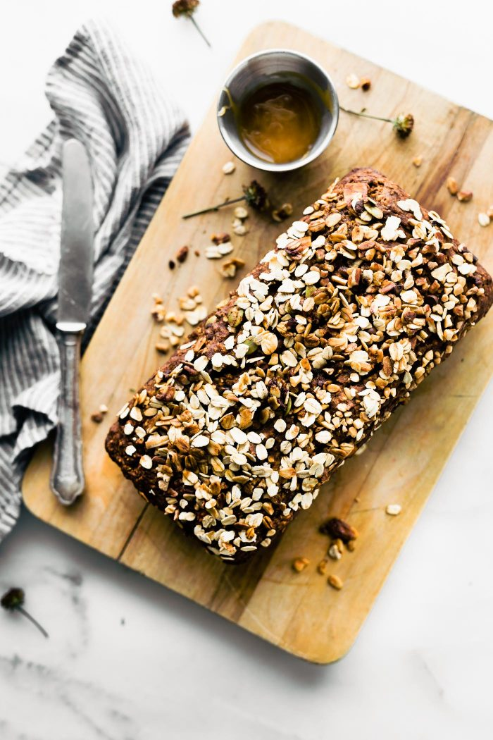 loaf of pumpkin oat flour bread topped with toasted oats