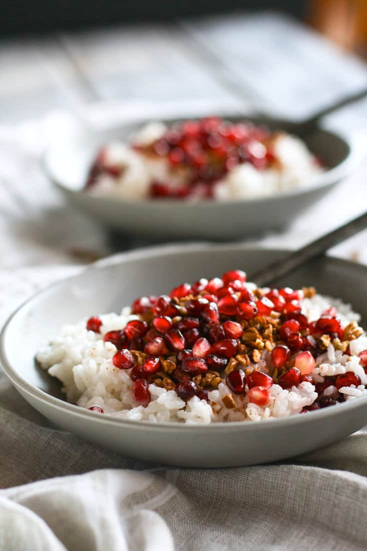 Coconut Rice and Pomegranate Porridge! Good carbs do exist! This gluten free and dairy free breakfast porridge makes for great performance fuel! A nourishing dish made with jasmine rice, coconut milk or cream, cinnamon, maple syrup, nuts, and cinnamon. The perfect combo of nutrient dense foods.