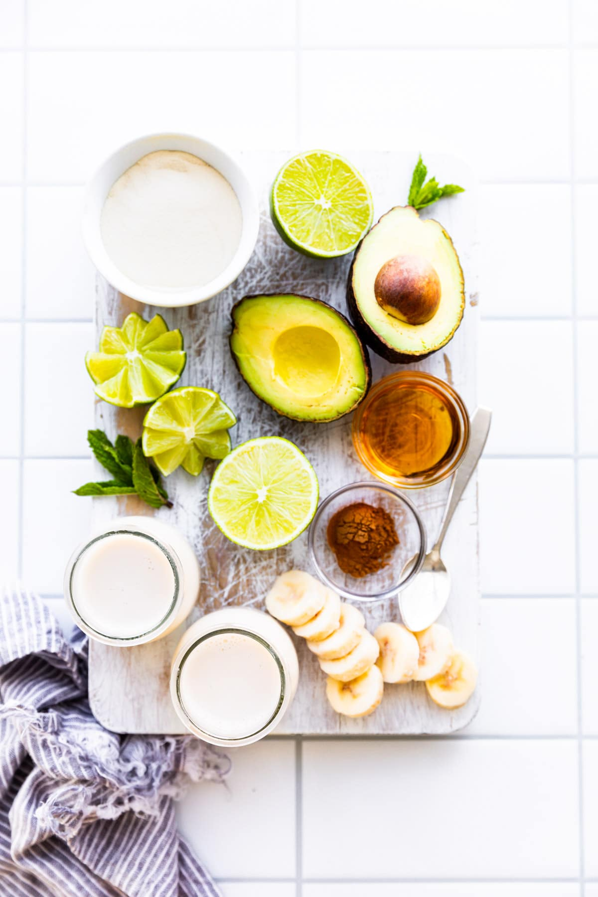 Ingredients on a wood board for dairy free smoothie recipe. Avocado, milk, protein, banana, lime, cinnamon