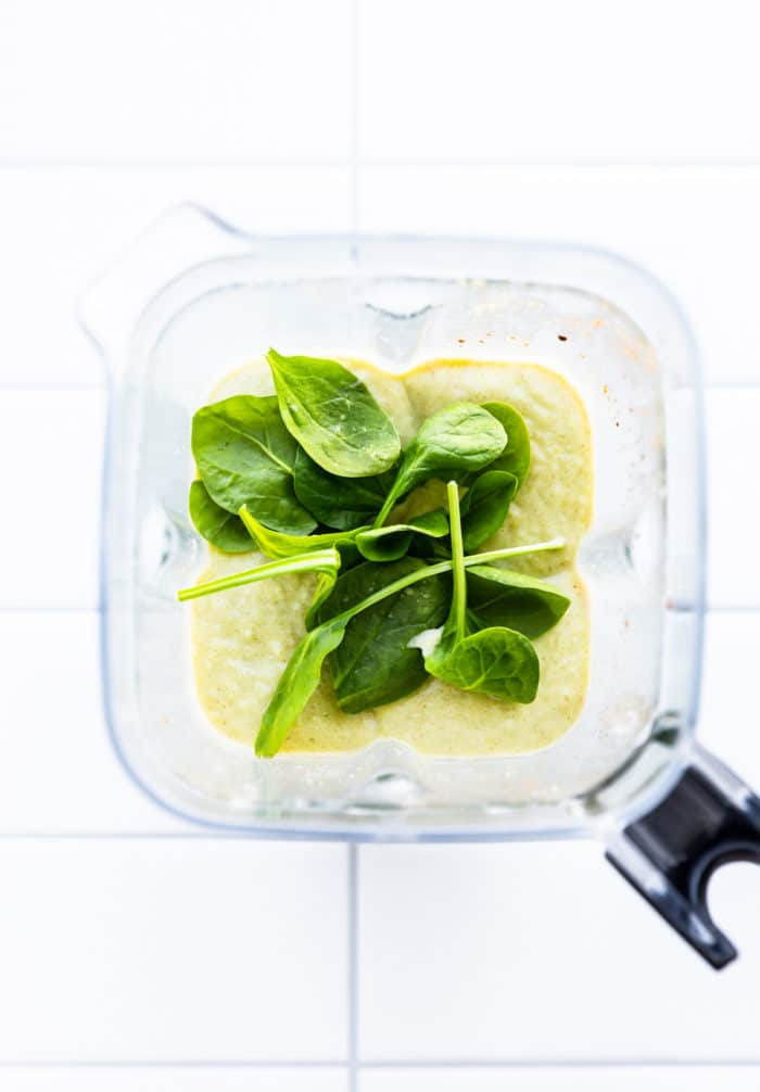 blender shot of keto avocado smoothie with spinach on top