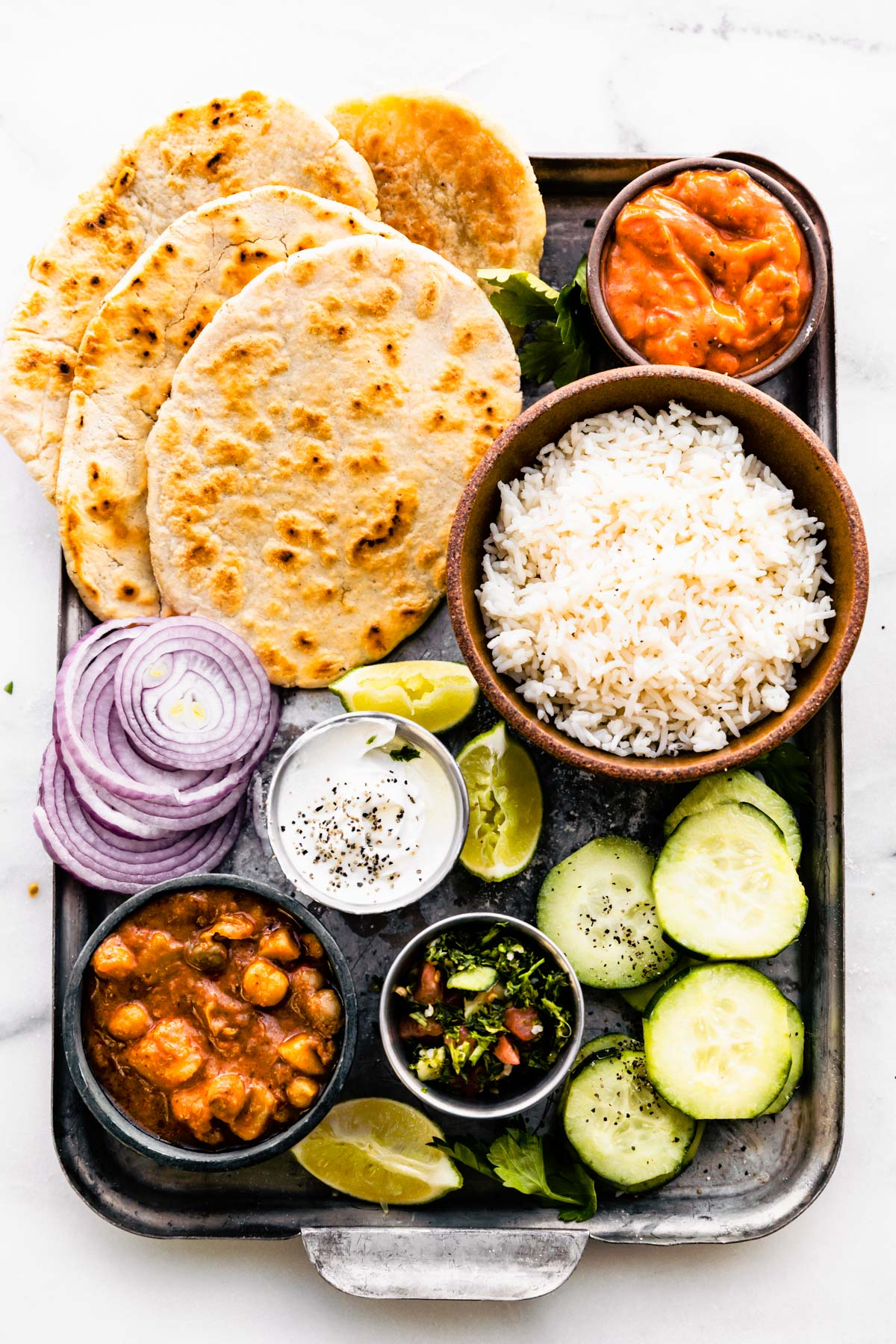 Grain Free Naan with Cassava Flour! Arranged on a pan with vegetables and curry dips plus rice. Back drop is green.