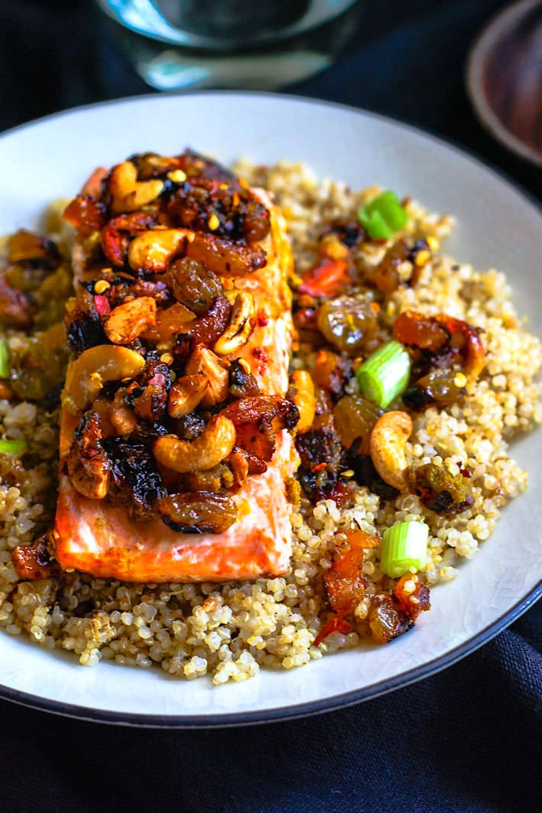 Green Curry Salmon and Cashew with Quinoa! Sweet and spicy green curry combined with cashews, salmon, and dried fruit! A healthy flavorful meal that is packed with anti-oxidants and comes together in 30 minutes! Great by itself or served on top of garlic quinoa.