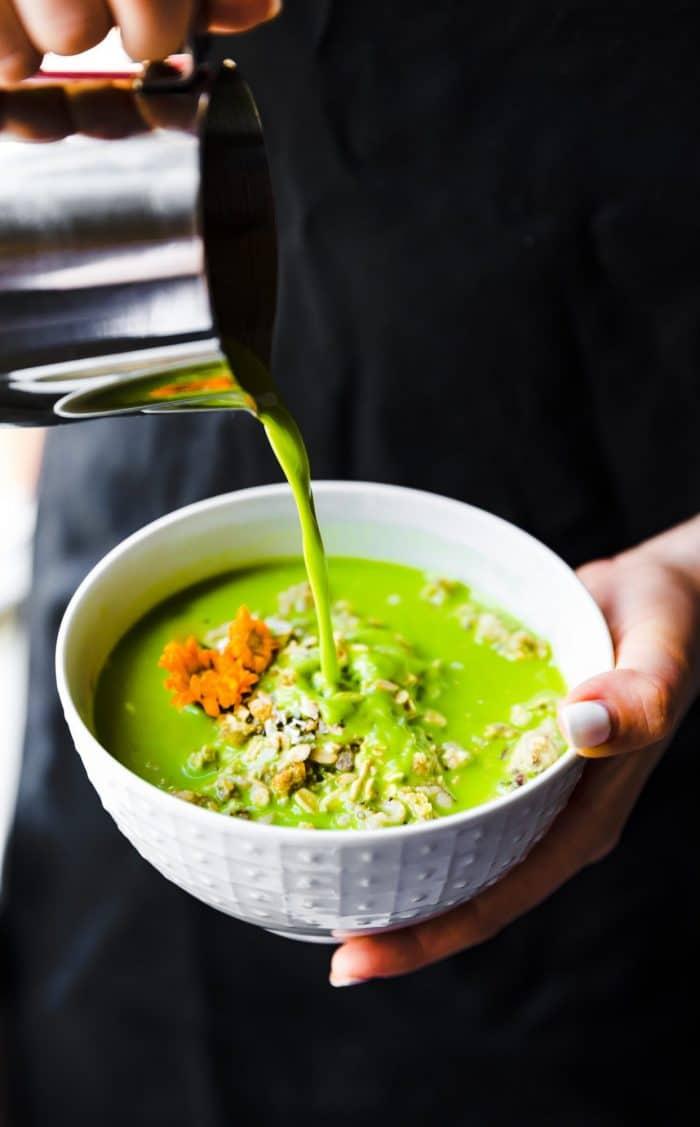 pouring green tea into a bowl of Coconut Matcha Green Tea Latte Oatmeal