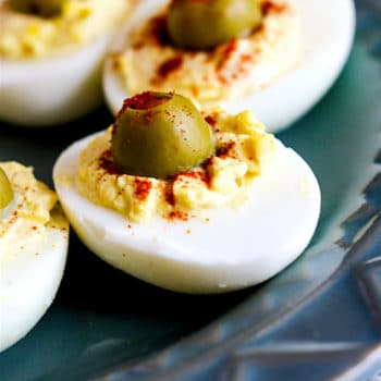 creamy deviled eggs with green olive in center