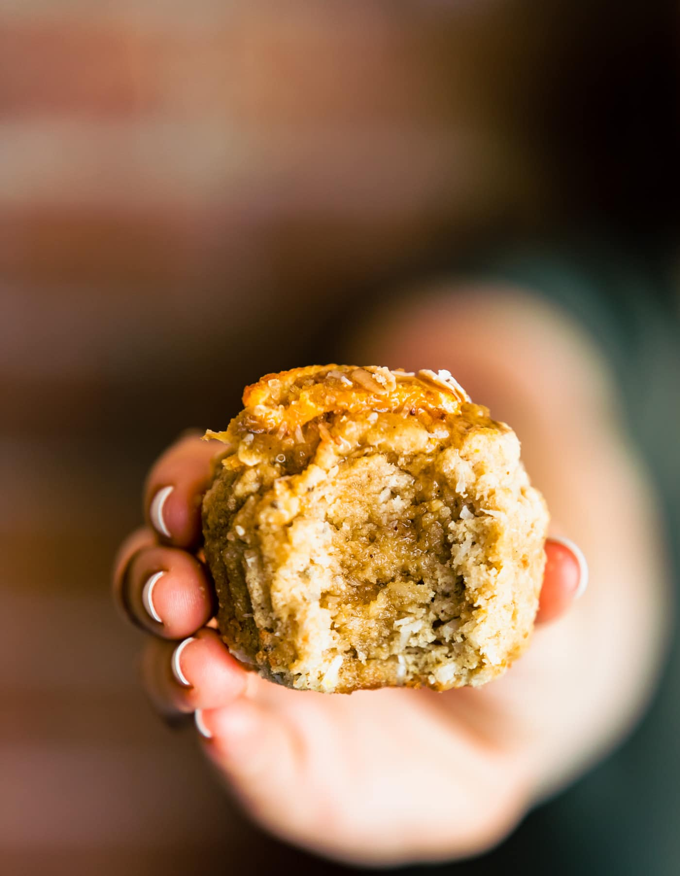 woman's hand with gluten free muffin with bite taken out, holding towards the camera