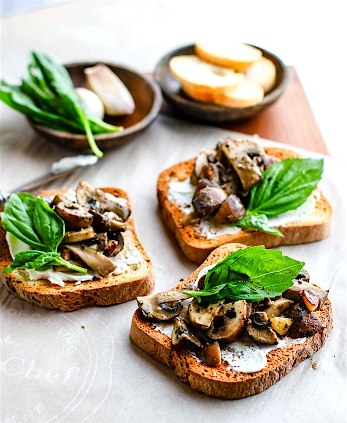 Simple creamy garlic herb mushroom toast recipe! This is one savory vegetarian gluten free appetizer that's packed full of flavor! Buttery sautéed garlic mushroom toast with cream cheese, cracked pepper, and basil made into one super easy and delicious gluten free snack or appetizer. It's a staple gluten free recipe I keep handy for parties, holidays, or even for a quick light meal.