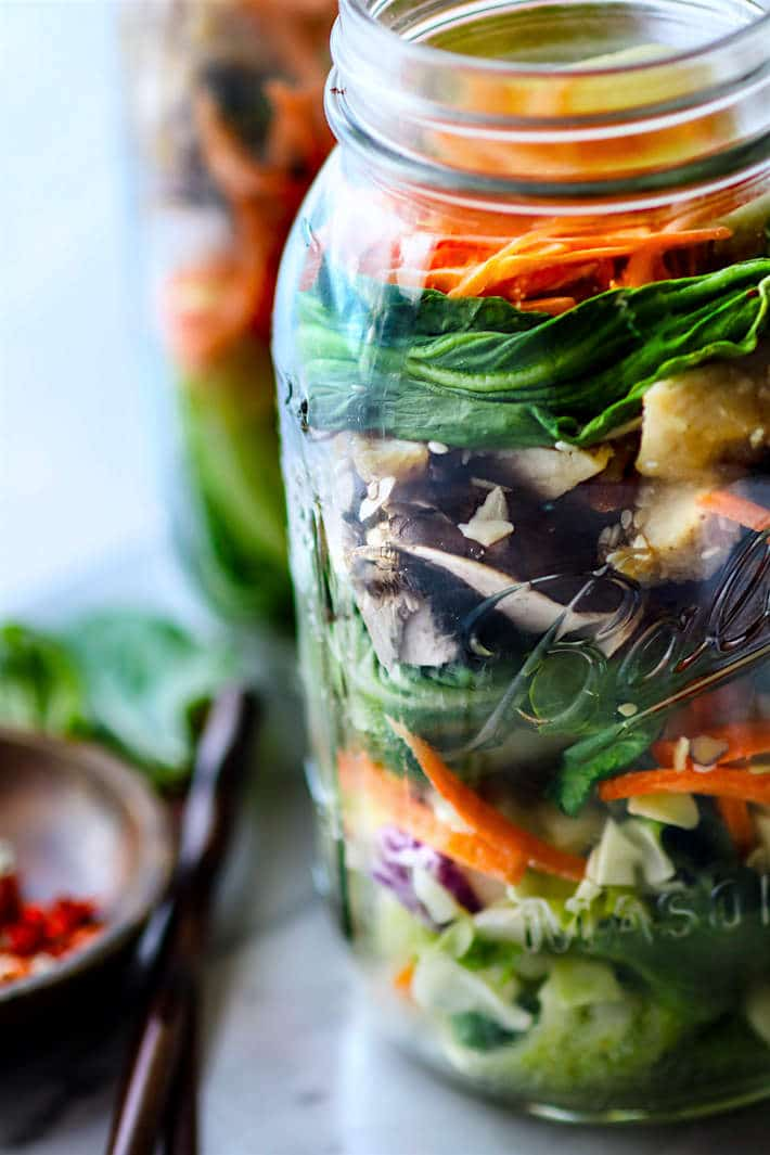 Easy Oriental Chicken Bok Choy Mason Jar Salads! Light, Gluten Free, and Paleo friendly oriental style mason jar salads that are great for lunch or dinners on the go! Perfect use of leftover vegetables and grilled or stir fried chicken as well. Portable Healthy lunches just got easy.