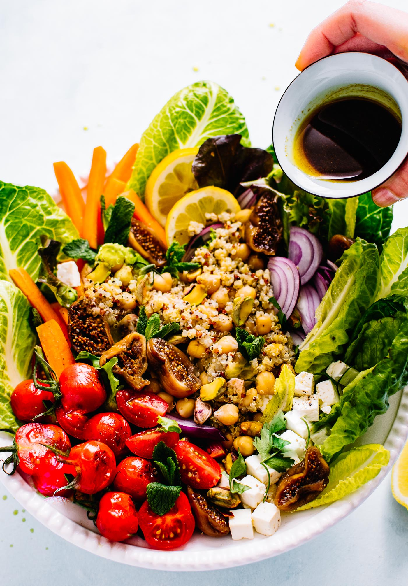 salad with dressing being poured