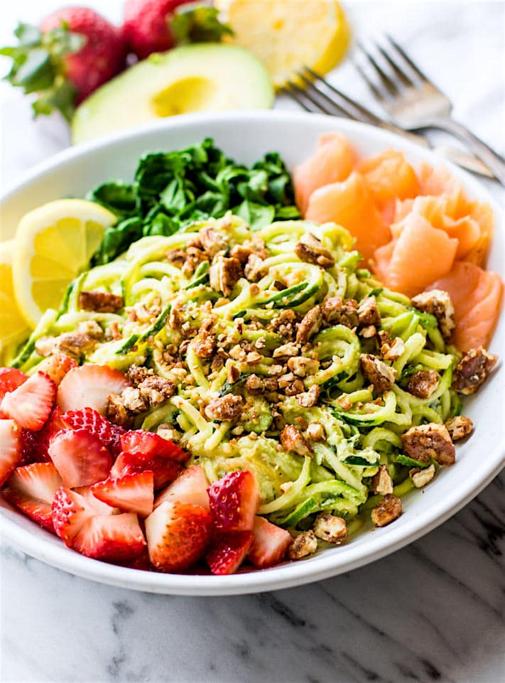 Smoked Salmon and Strawberry Zucchini Noodle Pasta Salad! A healthy lower carb Zucchini noodle pasta salad with a creamy avocado sauce and paired with the fresh strawberries, spinach, and smoked salmon. This gluten free Salad bowl is perfect for a spring or summer lunch or side dish. Clean ingredients, real food, UNREAL GOOD!