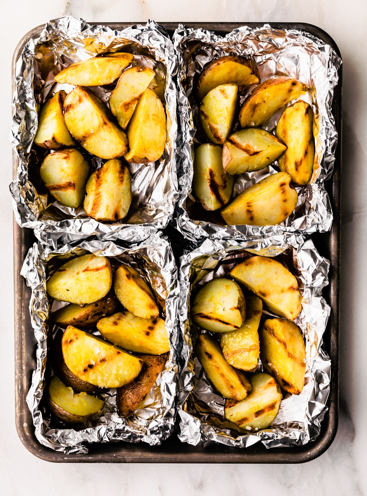 close up photo of grilled potatoes in aluminum foil packets