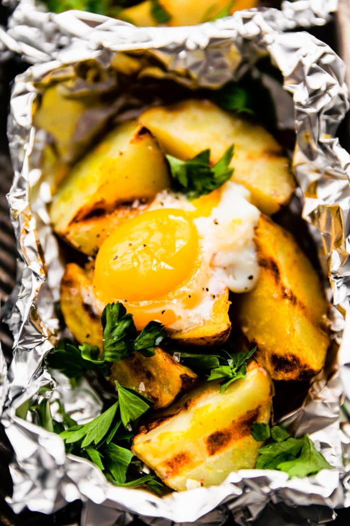 aluminum foil grilling packet dinner with baked potatoes and eggs
