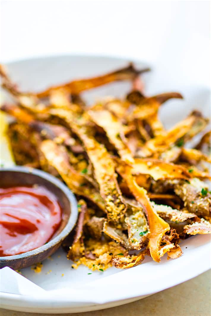 Healthy Oven Baked Parmesan Sweet Potato Skin Fries! Super simple oven baked sweet potato skin fries made from leftover potato skin peels. So crunchy, easy to make, and paleo friendly. Great snack or side dish that everyone loves!