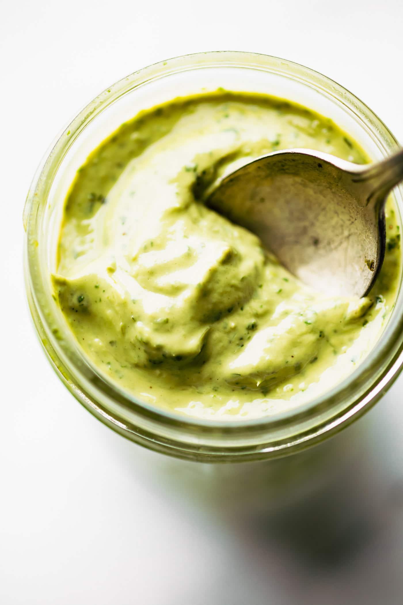 Overhead image of vegan green goddess dressing on a spoon over a mason jar