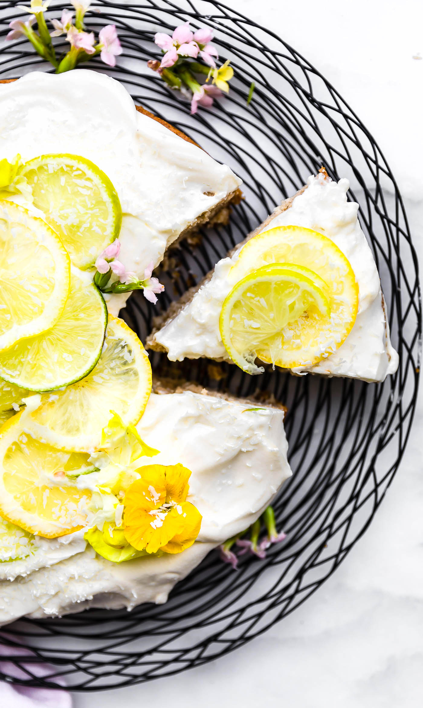 Super EASY gluten free lemon lime coconut vegan cake topped with fluffy whipped coconut cream frosting. An allergy friendly vegan cake that's perfect for Any season. So simple to make! All you need are a few REAL FOOD ingredients and 45 minutes to bake.
