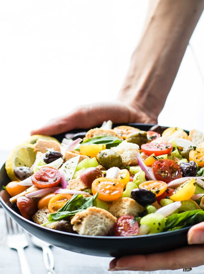 Toasted Panzanella Salad bowls! Toasted Crusty gluten free bread combined with juicy tomatoes, vegetables, and olives, all soaked in a zesty dressing. light, refreshing, and dairy free.