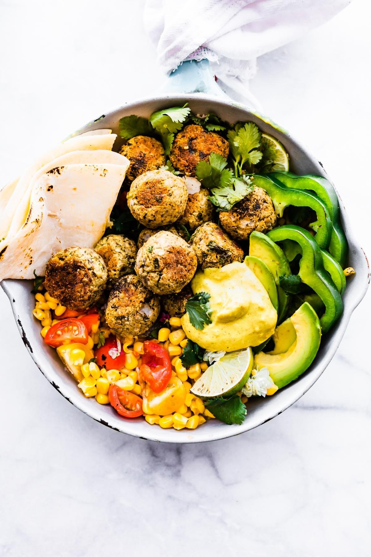 pan of falafel balls with veggies and sauce