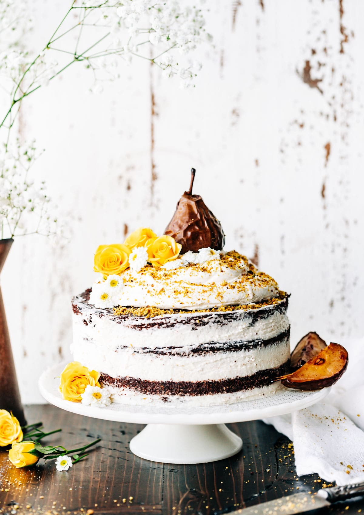 beautifully decorated naked cake with coconut frosting, edible flowers and glazed pear on top