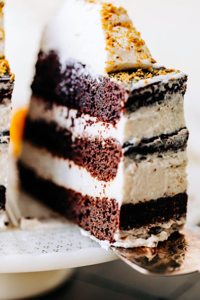 slice of chocolate almond flour cake with layers of coconut cream frosting