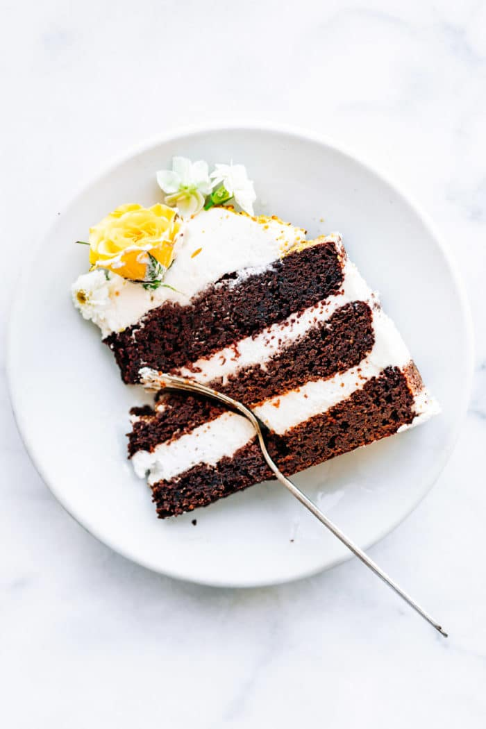 slice of chocolate layer cake on white plate with fork