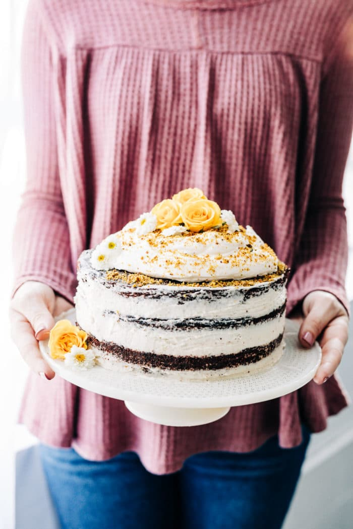 woman holding a white cake plate with grain free almond flour chocolate cake