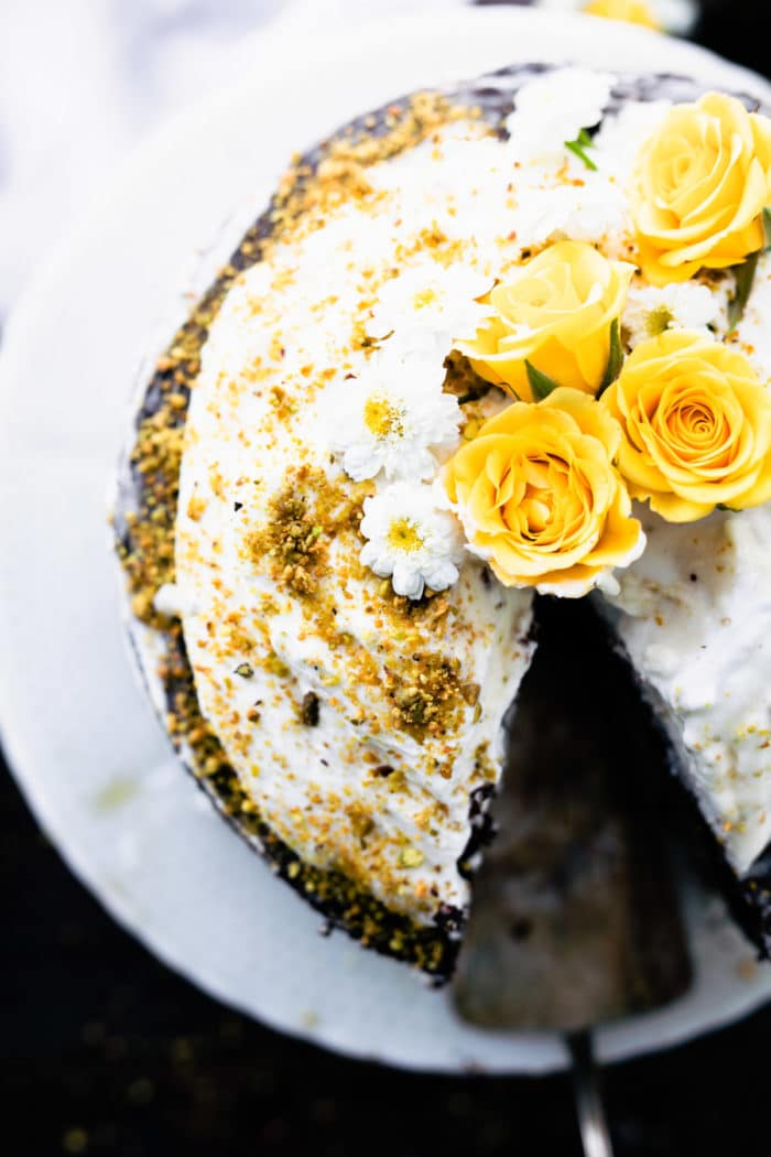 overhead image of frosted almond flour cake garnished with yellow roses