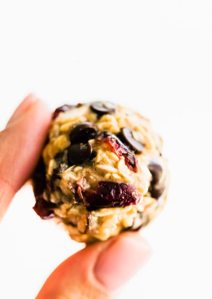 woman's fingers holding a healthy no bake oatmeal cookies energy bite