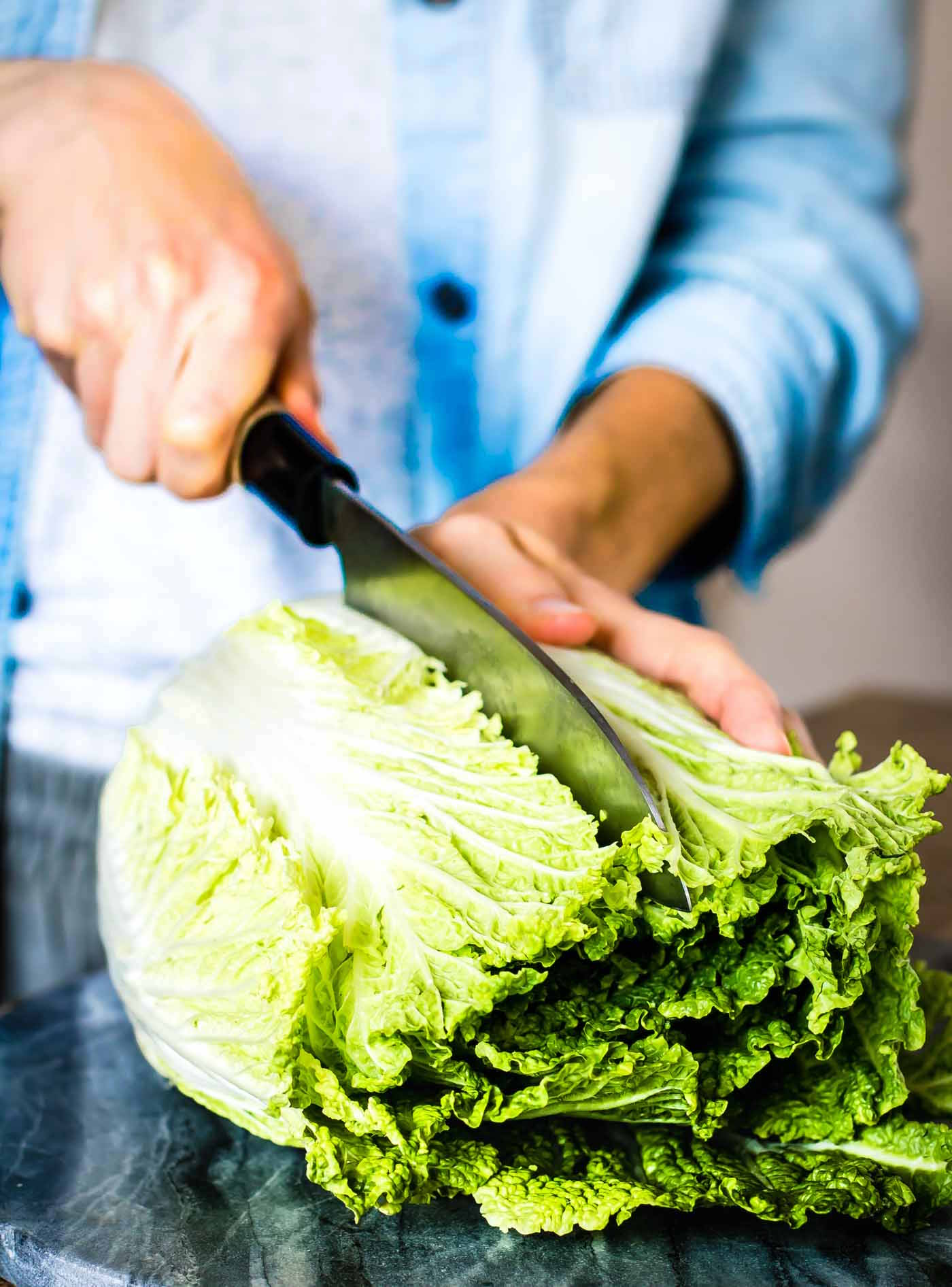 cutting into a head of Napa cabbage with a chef's knife