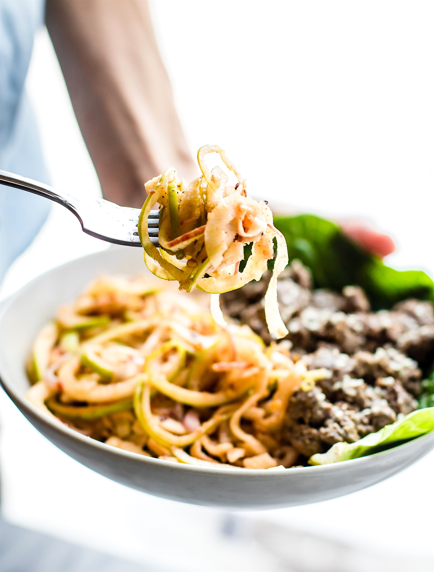 "Spiralized Apple ""kimchi"" salad with Garlic Beef! This Asian inspired spiralized apple salad makes a quick and healthy kimchi substitute. Red and Green Apple noodles combined in a spicy dressing with garlic beef. An easy Paleo power bowl meal ready in 20 minutes!"