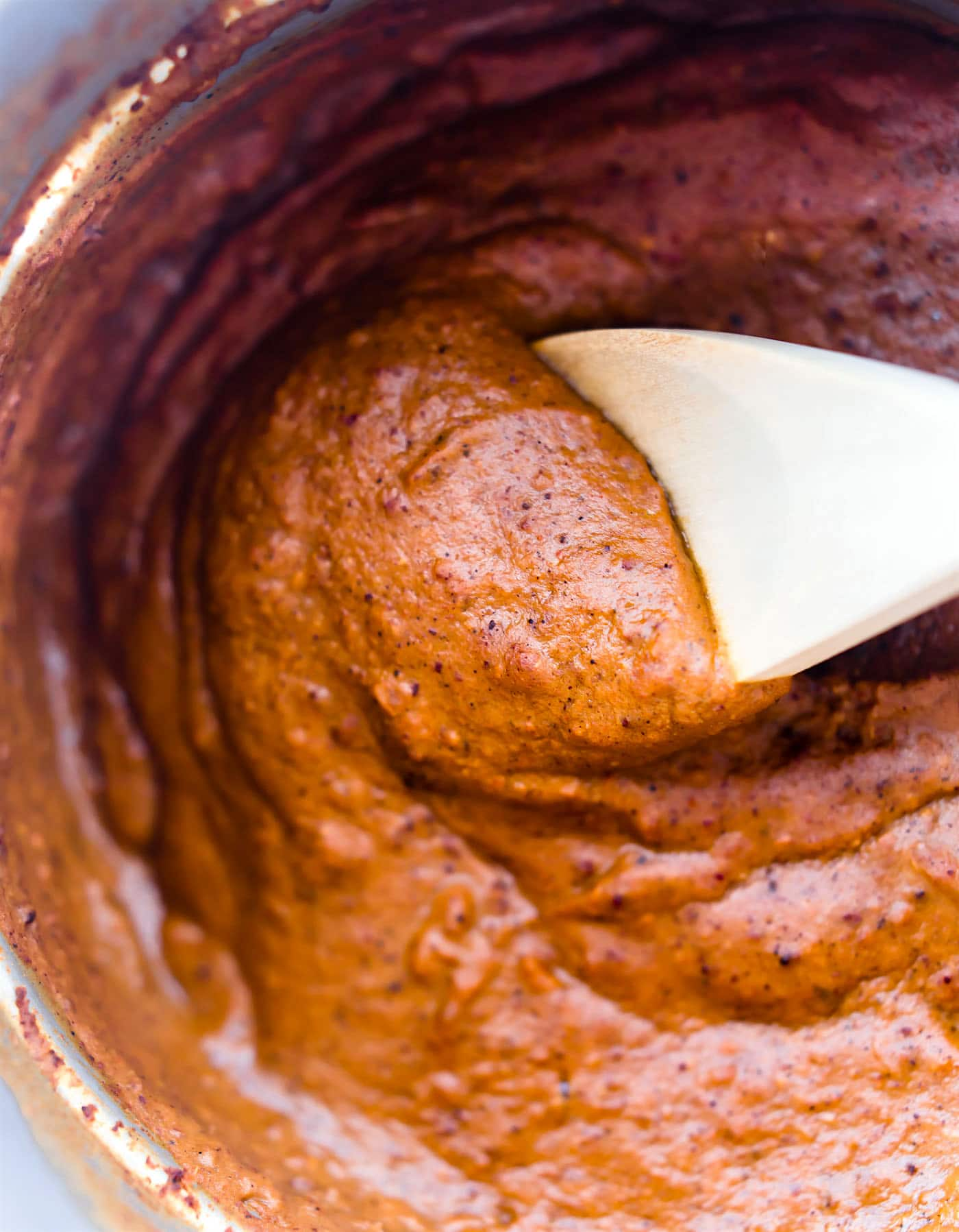 close up overhead image of creamy mole sauce in pot with wooden spoon