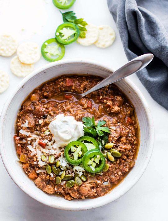 overhead image: bowl of mole sweet potato turkey chili garnished with cilantro and sour cream