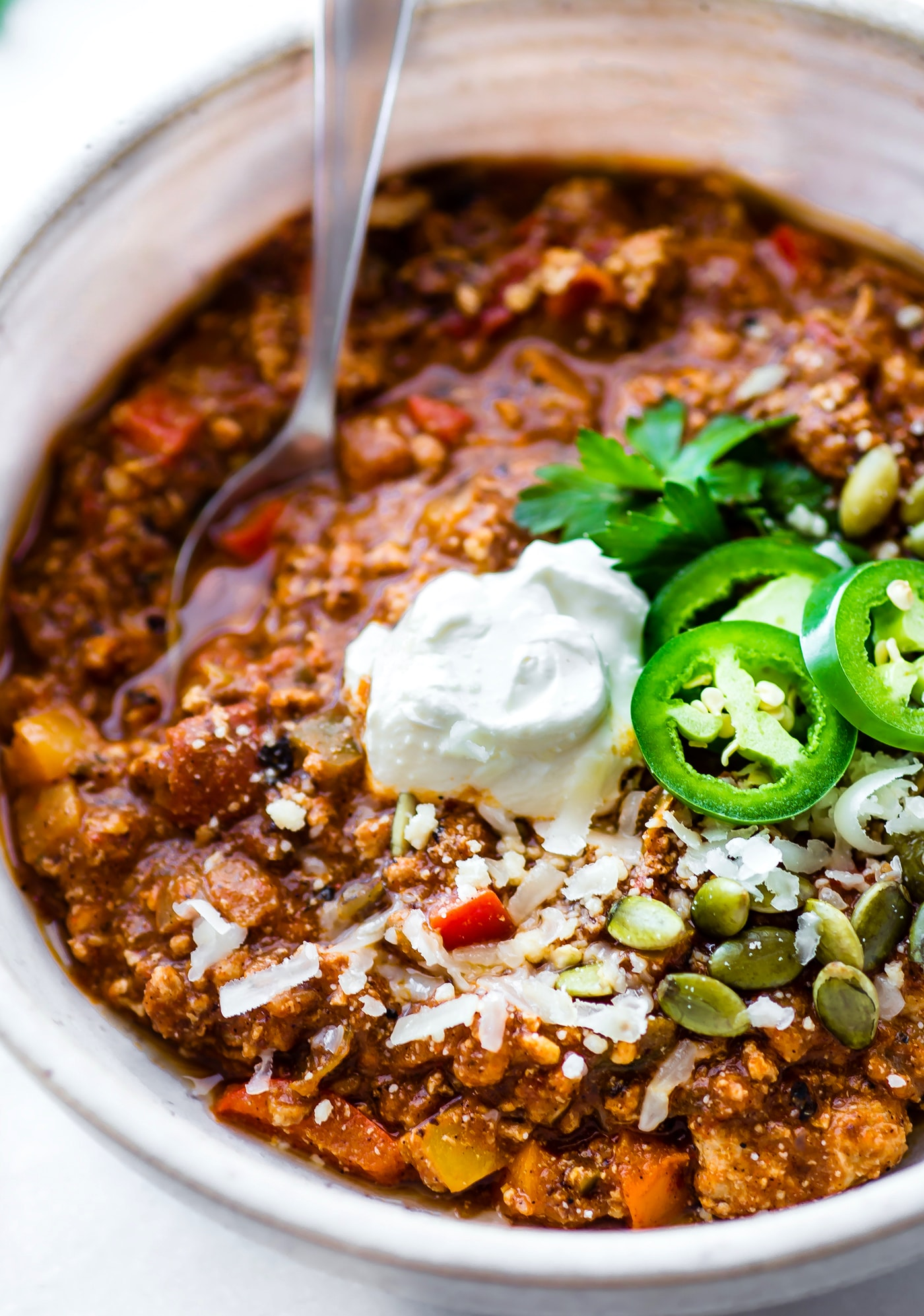 sweet potato chili topped with slices of jalapeno, shredded cheese and sour cream